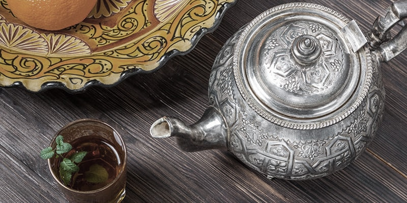 image of someone pouring tea out of a silver tea pot